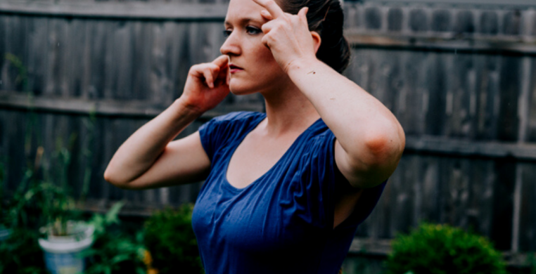 Dancer standing in the rainy backyard with her hands on her face