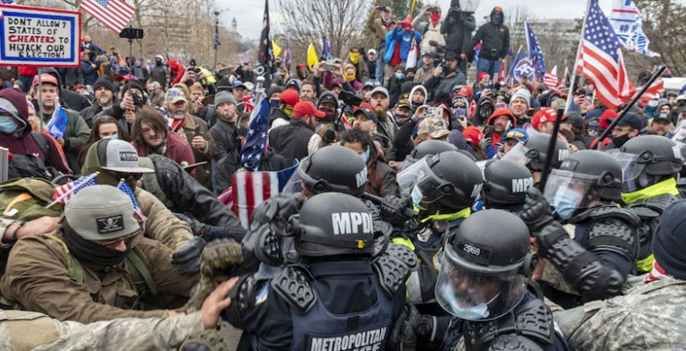 A mob of Trump supporters pushing against police forces on Jan. 6 at the U.S. Capitol. Photo by Blink O'fanaye on Flickr, via Creative Commons.